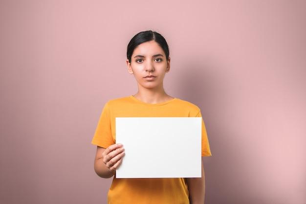 Triste pobre mujer morena en camisa amarilla con un cartel blanco limpio para agregar texto