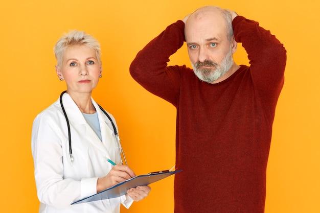 Triste practicante jubilada en bata médica blanca sosteniendo portapapeles diciéndole a su paciente anciano sobre diagnóstico y tratamiento
