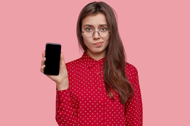 Triste señorita frunce los labios, sostiene un teléfono celular moderno con pantalla de maqueta, usa gafas transparentes, vestida con una camisa de lunares