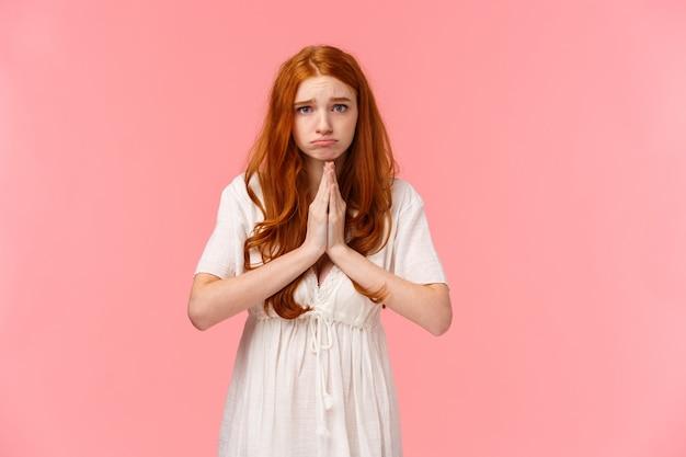 Triste y triste, linda niña pelirroja haciendo pucheros pidiendo ayuda, mirando a la cámara esperanzada, haciendo promesas o disculpándose, juntando las manos en oración, rogando favor, suplicando sobre rosa