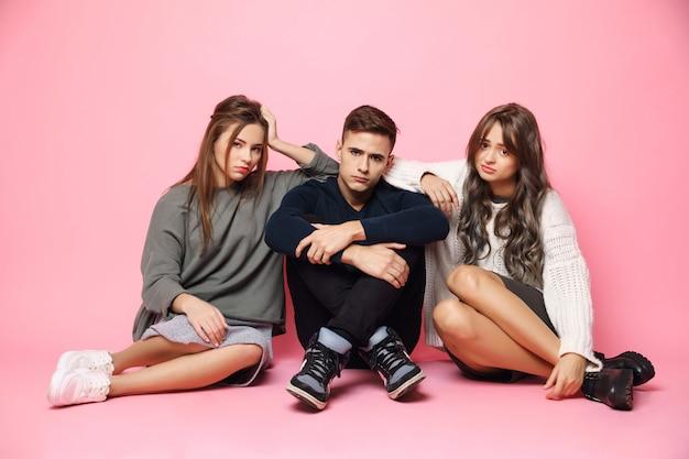 Tristes amigos jóvenes disgustados sentados en el piso rosa