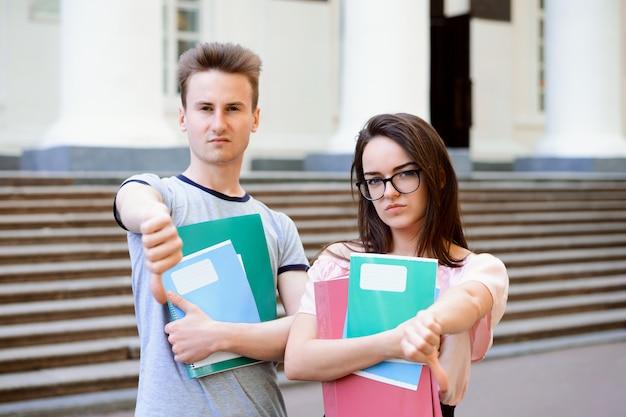 Tristes disgustados infelices jóvenes estudiantes mostrando los pulgares hacia abajo