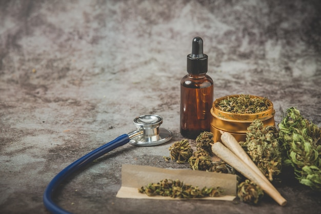 Trituradora de metal, aceite de cannabis y articulación en posar