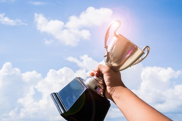 Trofeo campeón ganador colocado en la mano levantada sosteniendo