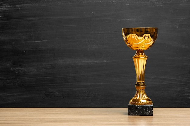 Trofeo de oro en un escritorio de madera.