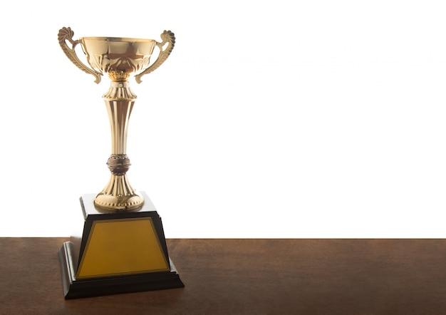 Trofeo de oro en mesa de madera.