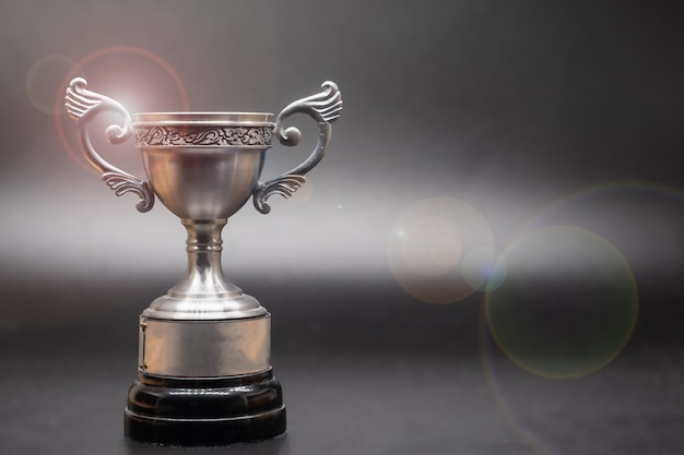Trofeo de plata encima de la vieja mesa de madera frente a la pizarra.