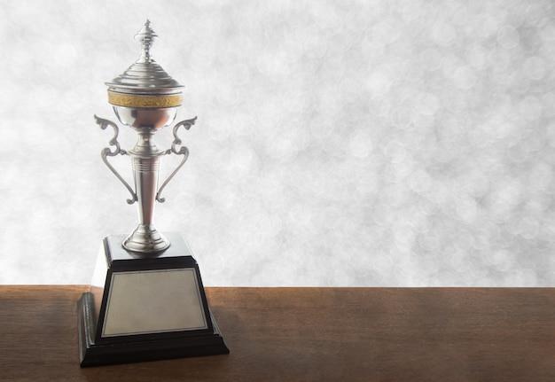 Trofeo de plata en mesa de madera.