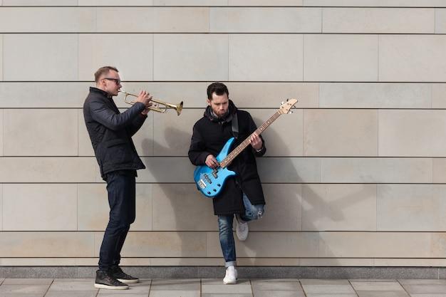 Trompetista y guitarrista tocando en frente de un muro