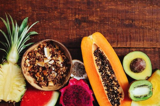 Trópico de frutas frescas de verano y semillas de granola sobre fondo de madera marrón