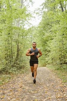 Trotar en el bosque. atleta corriendo por el bosque.