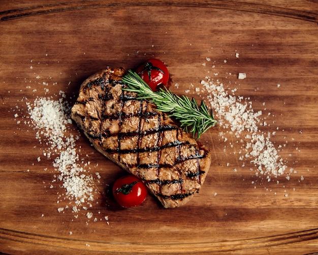 Trozo de bistec y tomates bien fritos sobre una tabla de madera