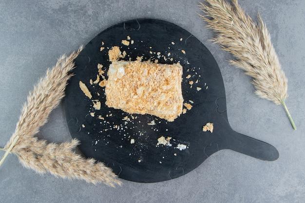 Un trozo de delicioso pastel de napoleón en un tablero oscuro