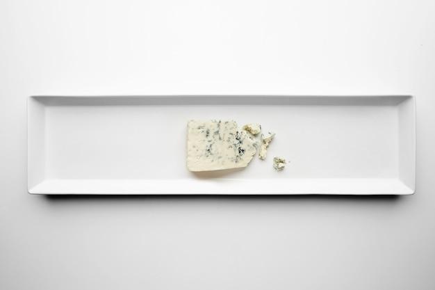 Trozo de gorgonzola aislado en plato blanco