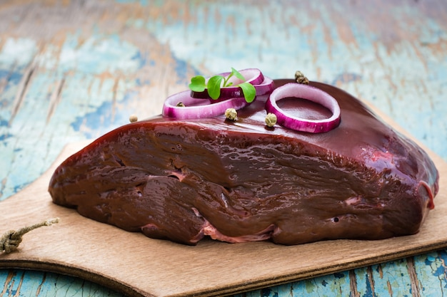 Un trozo de hígado de res crudo en un tazón con ingredientes para cocinar en una mesa de madera