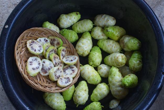 Trozo de noni con fruto de noni en la palangana negra.