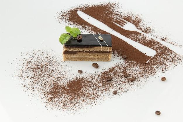 Un trozo de pastel espolvoreado con azúcar en polvo sobre un fondo blanco.