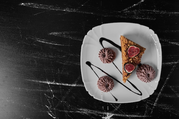 Un trozo de pastel con galletas de cacao en un plato blanco.