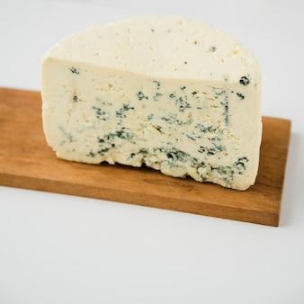 Trozo de queso azul en la tabla de madera contra el fondo blanco