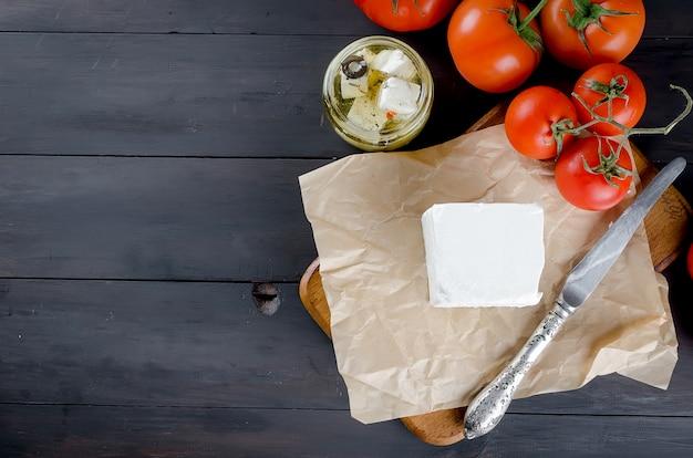 Trozo de queso blando en el tablero y feta marinado en un frasco y tomates para ensalada.