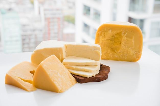 Trozo de queso cheddar y gouda en una mesa blanca cerca de la ventana