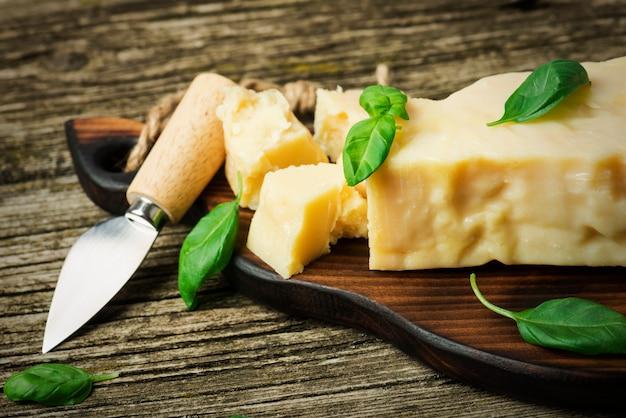Un trozo de queso parmesano con hojas de albahaca y un cuchillo de queso sobre una tabla de madera