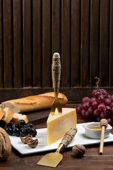 Trozo de queso parmesano con tenedor de queso en la parte superior, servido con miel, uva