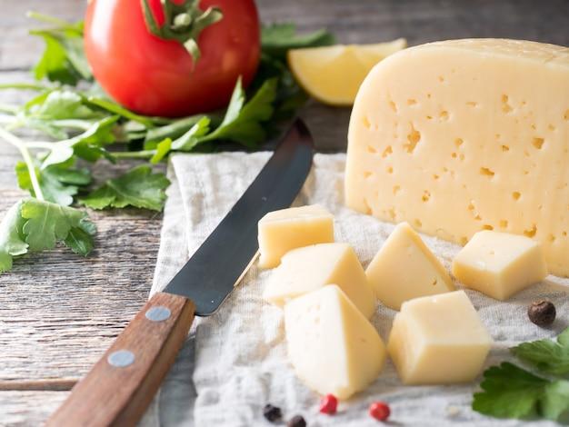 Trozo de queso con perejil, tomates en una toalla de lino fondo de madera rústico.