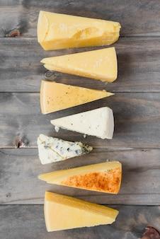 Trozo de queso triangular dispuesto en fila en tablón de madera