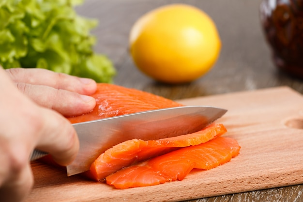 Un trozo de salmón ahumado. sobre una tabla para cortar madera con un cuchillo.