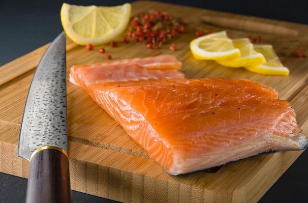 Un trozo de salmón salado en una tabla de cortar con limón y un cuchillo