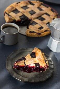 Un trozo de tarta de cerezas descansa sobre un plato de cerámica y una taza de café con una jarra de leche sobre la mesa