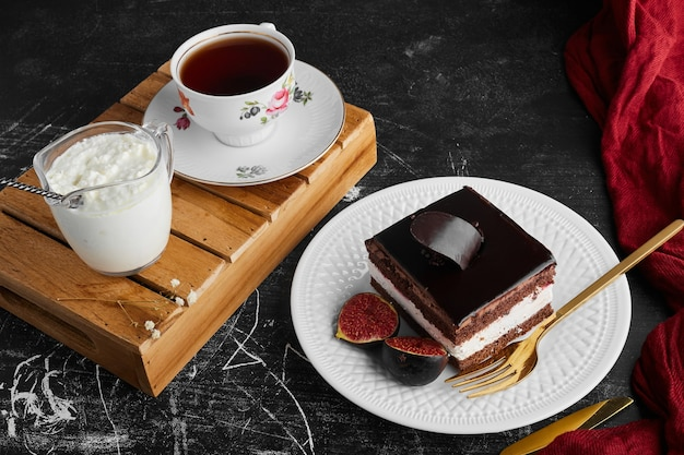 Un trozo de tarta de chocolate con frutas y una taza de té y cuajada.