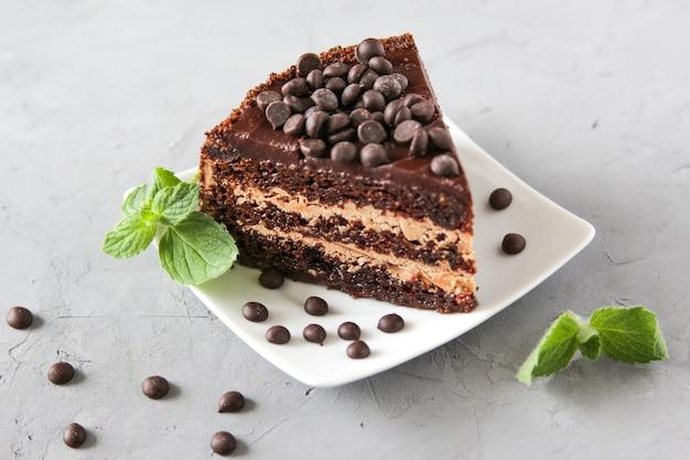 Trozo de tarta de chocolate en un plato blanco con chocolate y menta