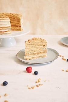 Trozo de tarta con crema y una miga de cobertura en un plato sobre la mesa