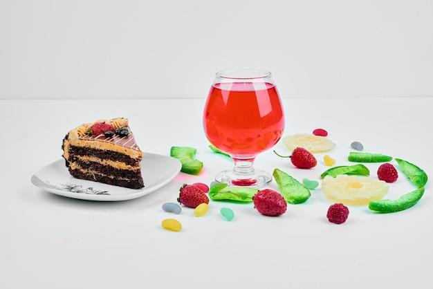 Un trozo de tarta con frutas y bebida.