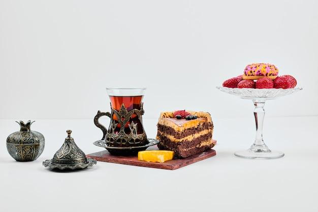 Un trozo de tarta con frutas y té.