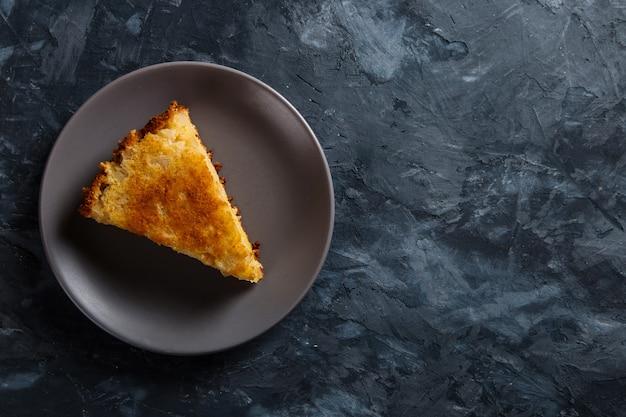 Un trozo de tarta de manzana en un plato gris, sobre un fondo concreto.