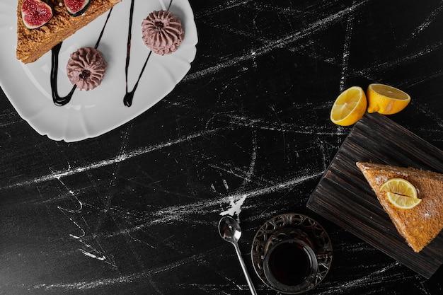 Un trozo de tarta medovic sobre piedra negra servido con confitura y galletas.