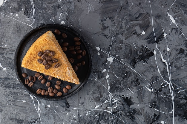 Trozo de tarta napoleón y granos de café en una placa de madera, sobre la mesa mixta.