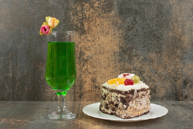 Un trozo de tarta con un vaso de jugosa limonada verde en la pared de mármol