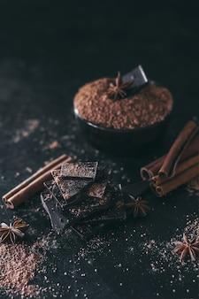 Trozos de barra de chocolate con cacao en polvo en la oscuridad