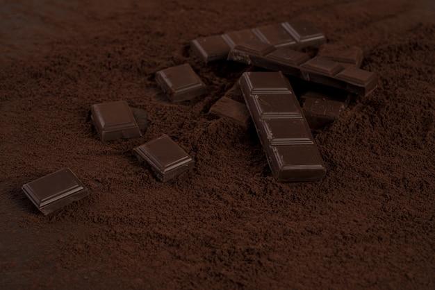 Trozos de barra de chocolate cubiertos de chocolate en polvo