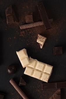 Trozos de barra de chocolate y dulces sobre superficie de madera