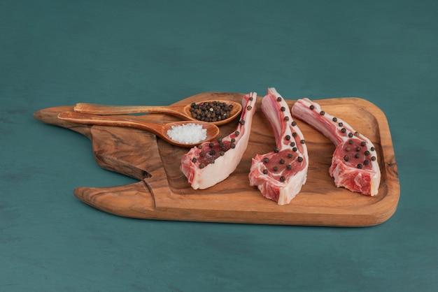 Trozos de carne cruda sobre tabla de madera con granos de sal y pimienta.