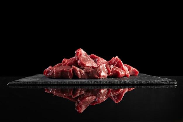 Trozos de carne fresca cruda aislados en negro sobre tablero de piedra vista lateral reflejada