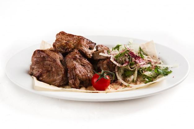Trozos de carne a la parrilla en un plato blanco con hierbas y verduras
