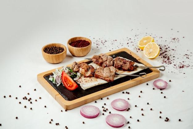 Trozos de carne en un pincho con cebolla en una tabla de madera