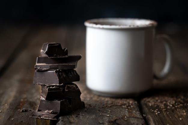 Trozos de chocolate apilados con una taza de cerámica blanca