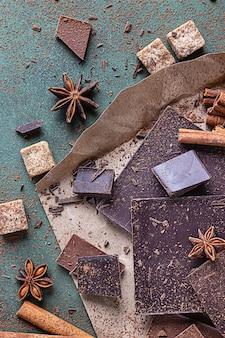 Trozos de chocolate, cacao en polvo, canela, estrella de anís y panela. concepto de ingredientes de cocina.